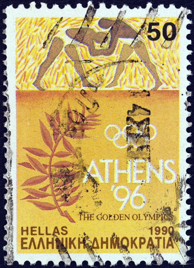 GREECE - CIRCA 1990: A stamp printed in Greece shows wrestlers and olive branch, circa 1990. royalty free stock photography