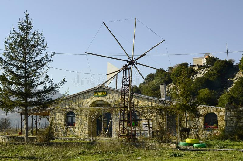 Greece, Crete, Lassithi Plateau. Crete, Greece - December 26, 2013: Restaurant and wind wheel outside the season situated on Lassithi plateau stock photos