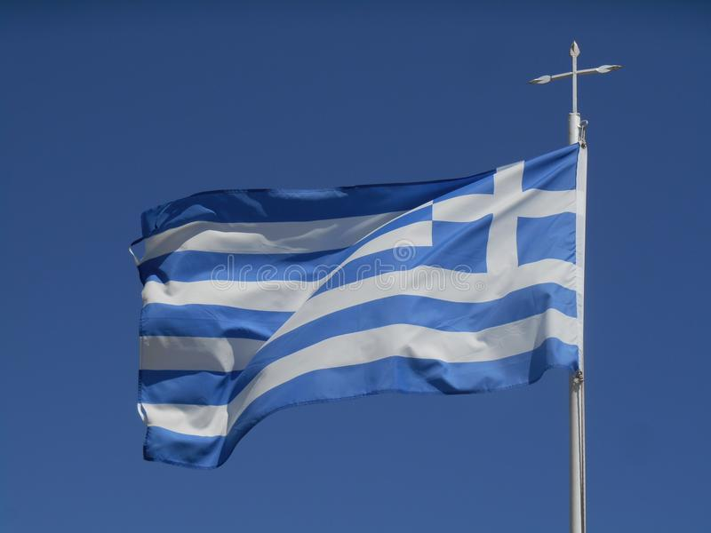 Greece flag hovering in sky. Photo of blue and white Greece flag hovering in sky, sunny day stock image