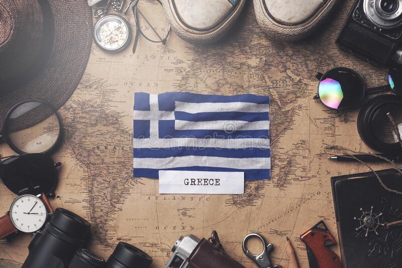 Greece Flag Between Traveler`s Accessories on Old Vintage Map. Overhead Shot.  stock photos