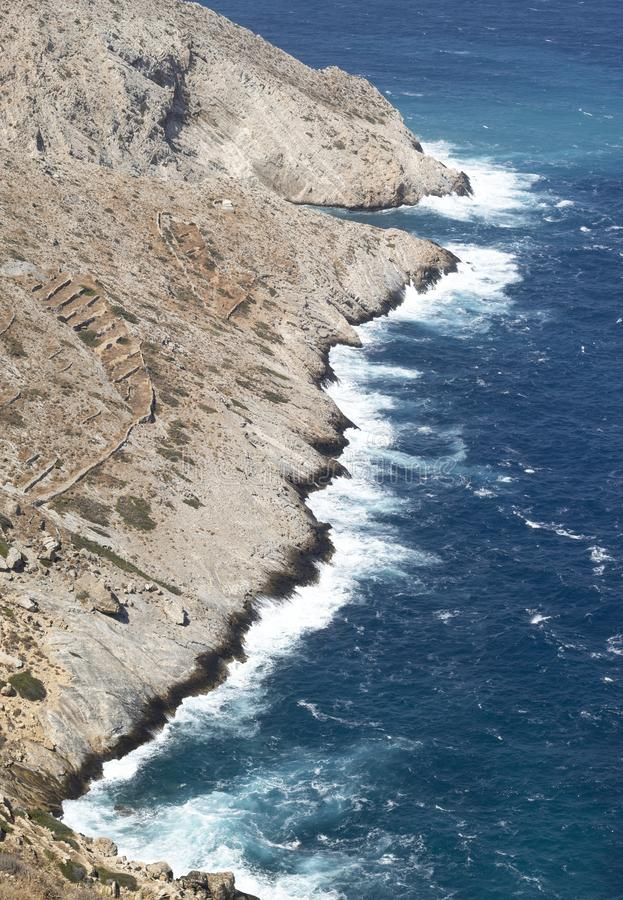 Greece, Folegandros. Waves and sea spray on a windy day. Greece, the island of Folegandros. Sheer cliffs seen from the islands capital the Hora.  Waves and sea royalty free stock photography