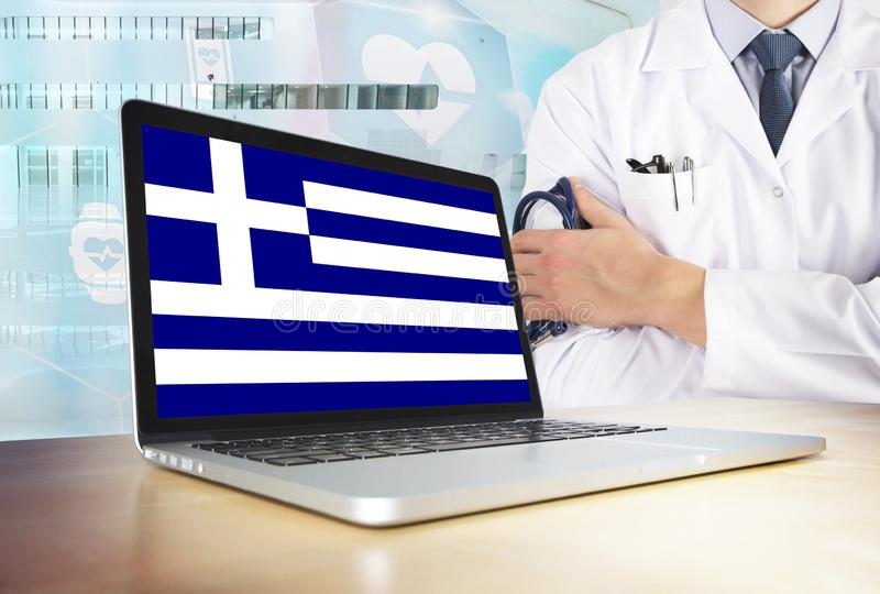 Greece healthcare system in tech theme. Greek flag on computer screen. Doctor standing with stethoscope in hospital. Cryptocurrency and Blockchain concept royalty free stock photography