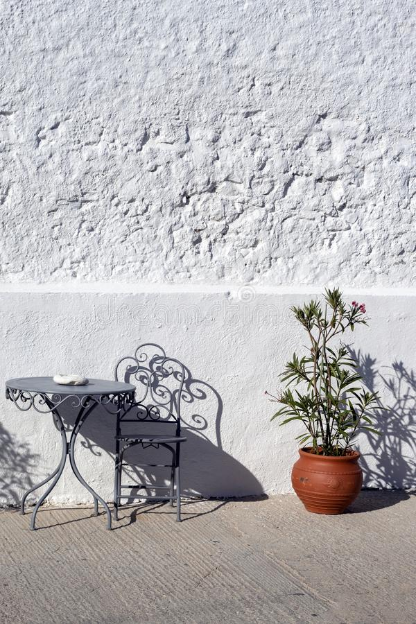 Greece,Folegandros. Chairs, table and plant. Greece, the island of Folegandros.  Late afternoon with lengthening shadows,  Metal tables and chairs against a royalty free stock photo