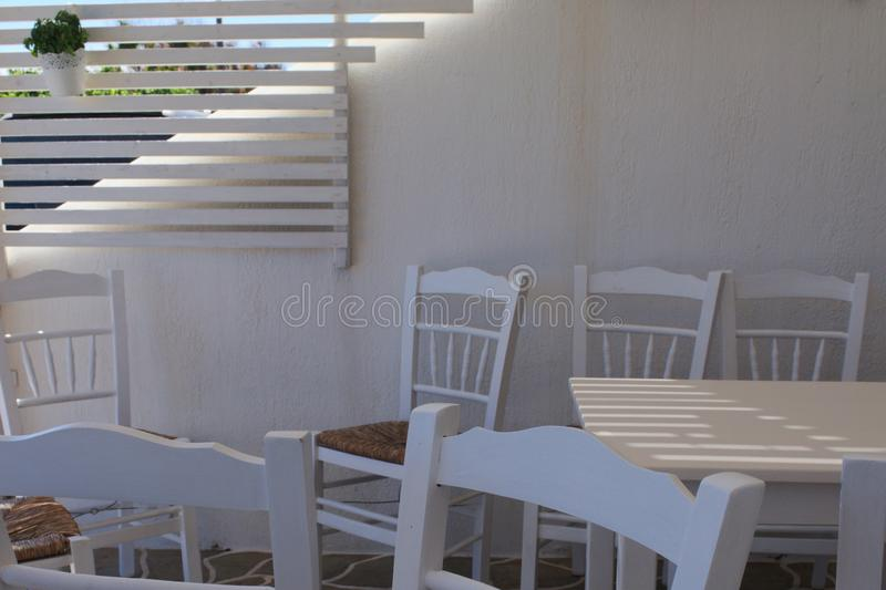 Greece, the island of Sikinos.White painted furniture in a taverna. royalty free stock photos