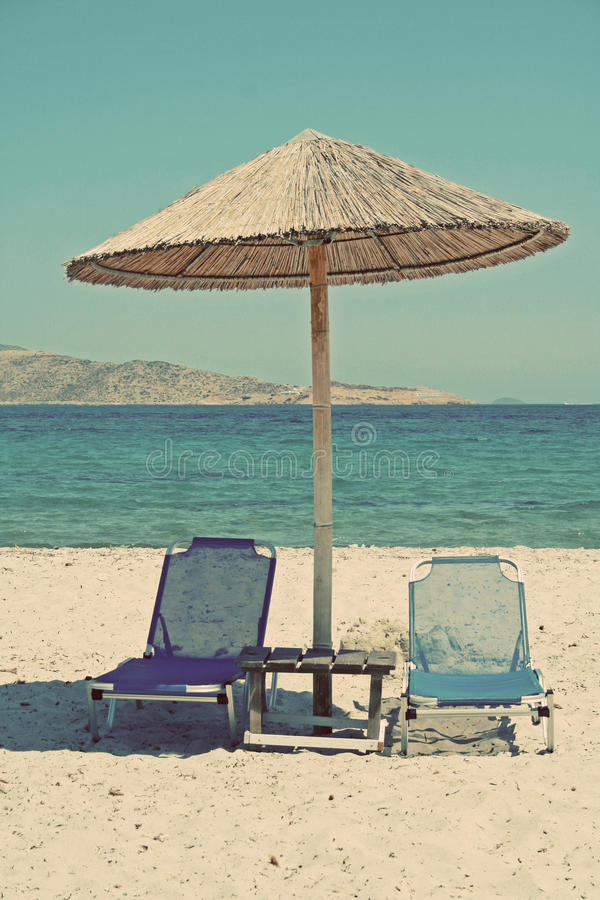 Greece. Kos island. Two chairs and umbrella on the beach. In ins royalty free stock image