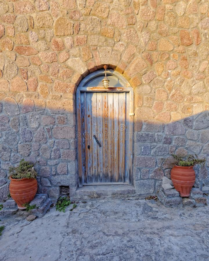 Greece, old house door and flowerpots between light and shadow stock images