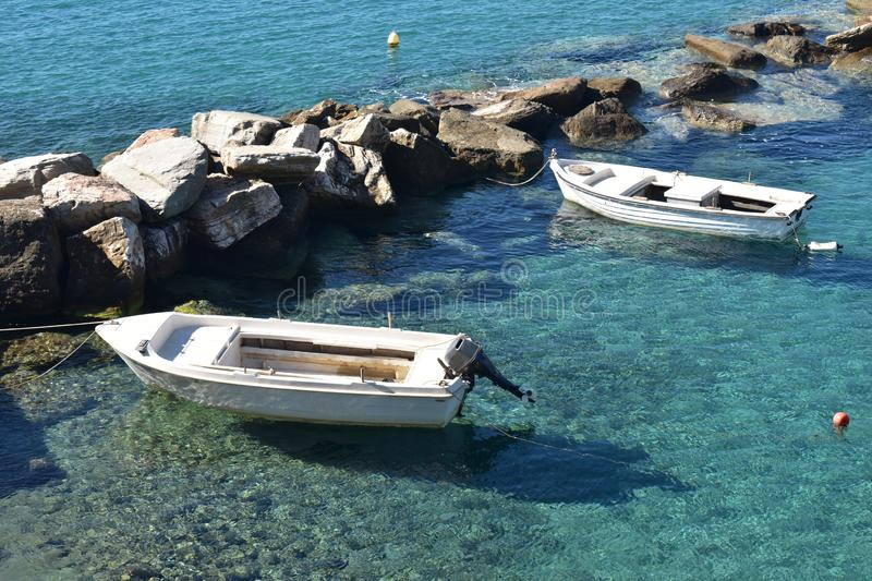 Greece the island of Sikinos. Two boats moored in the still waters of the harbour. royalty free stock images