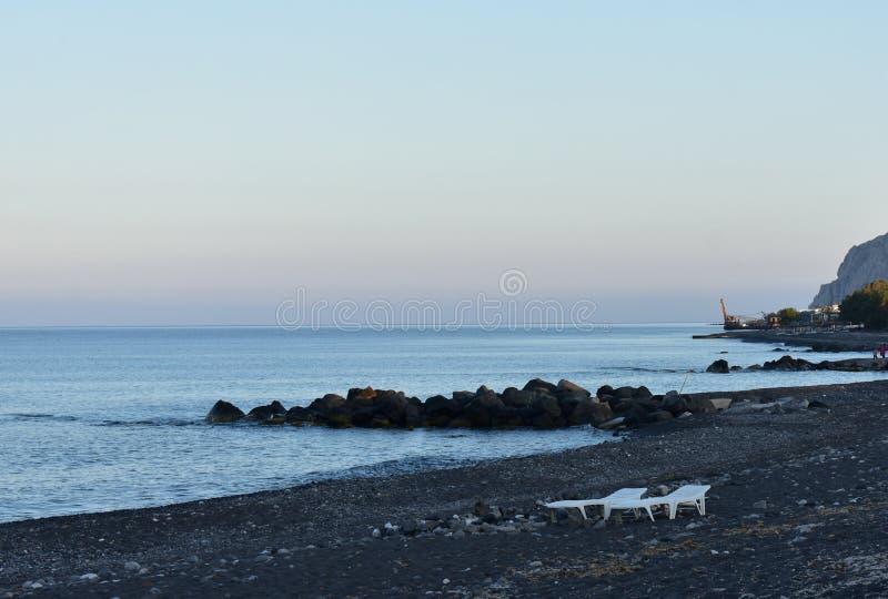 Greece, Santorini.  The dark sand beach at Monolithos as the sun sets. Greece, the island of Santorini.  The dark sand beach at Monolithos as the sun sets on a royalty free stock image