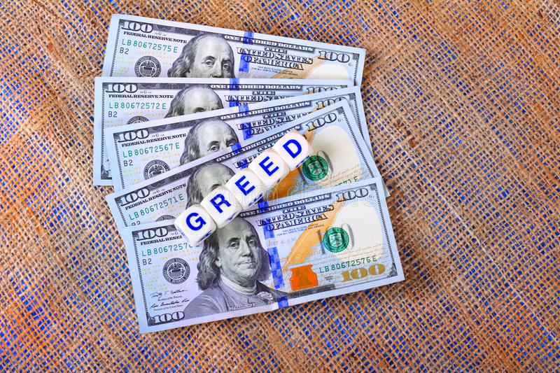 Greed. 5 new style 100 dollar bills legal tender fanned out closeup on burlap as a background and dice with the word greed spelled out laying on top royalty free stock image