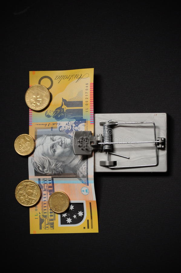 Australian money in mouse trap. Australian money coins and notes in a mouse trap symbolising financial greed and temptation stock photography