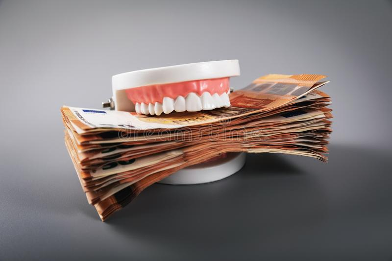 Greediness concept - teeth model eating euro money bills. On gray background stock photography