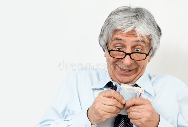 Greedy. Gray-haired greedy businessman with banknotes in his hands. Focus on the face royalty free stock photography