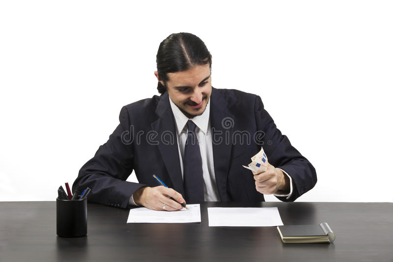 Greedy ambitious man working at his desk royalty free stock image