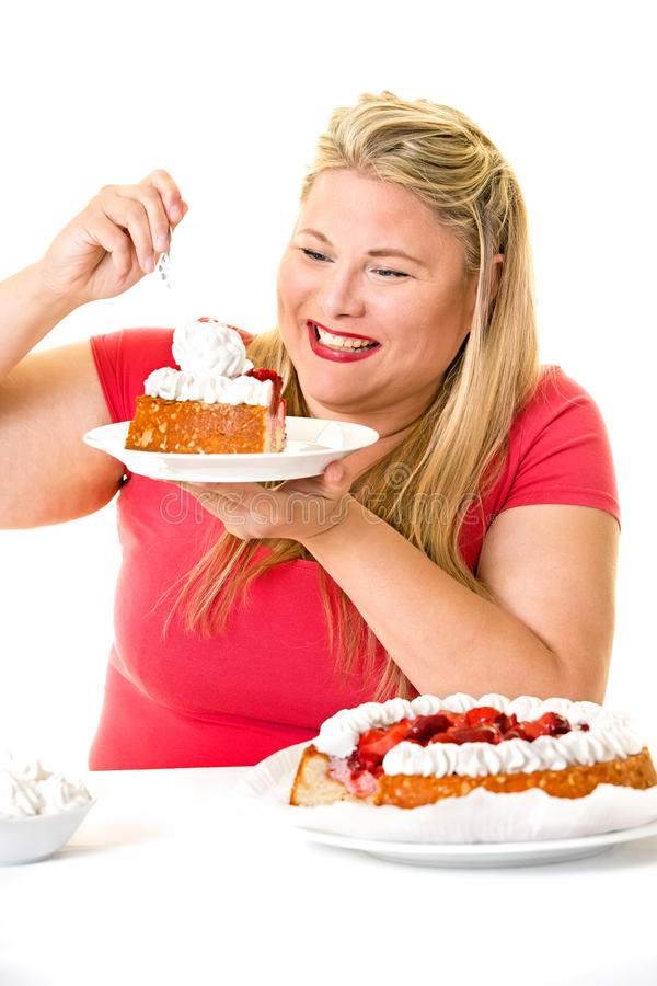 Greedy blond woman with fattening cream cakes. Greedy smiling overweight blond woman with fattening cream cakes royalty free stock photography