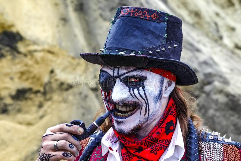 Greedy evil look of a pirate with patch over one eye and a pipe in his mouth royalty free stock images