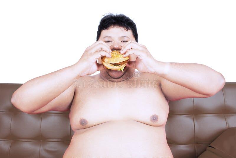 Greedy fat man eating hamburger on studio royalty free stock photo