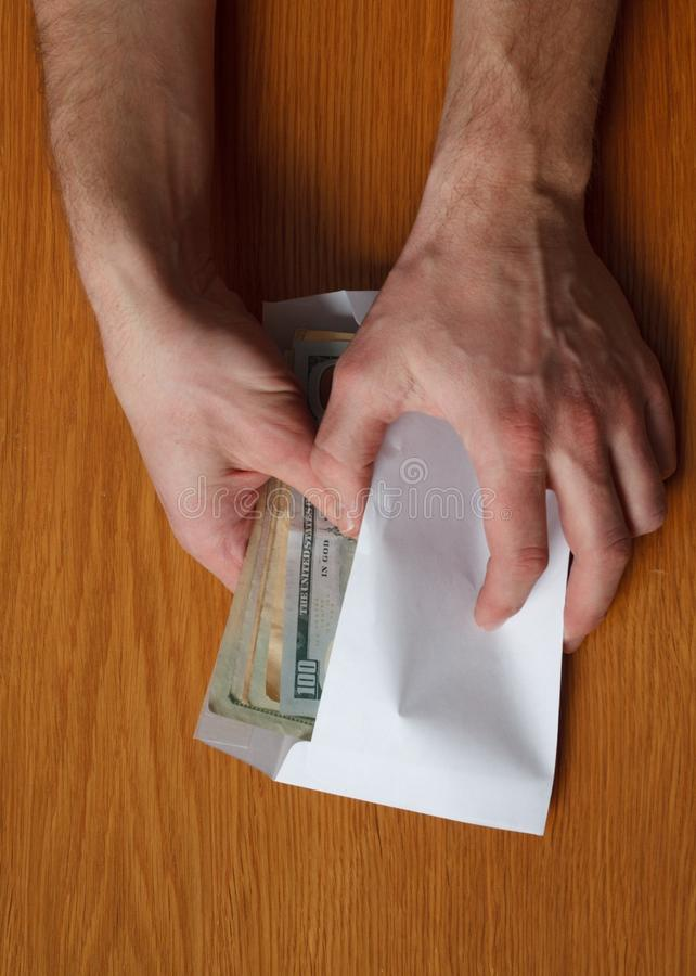 Greedy hairy man`s hands takes a bribe of some US dollars banknotes in the office at the table. Greedy man`s hands takes a bribe of some US dollars banknotes in royalty free stock photo