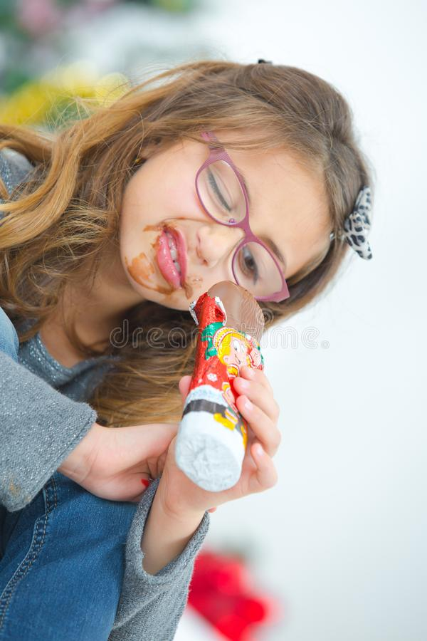 Greedy little girl eating chocolate stock photo