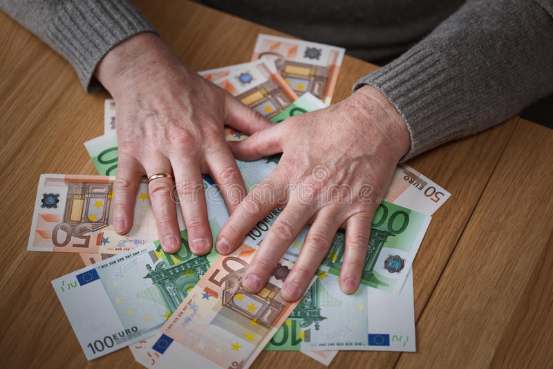 The greedy man closes hands Euro banknotes. View from above stock photo