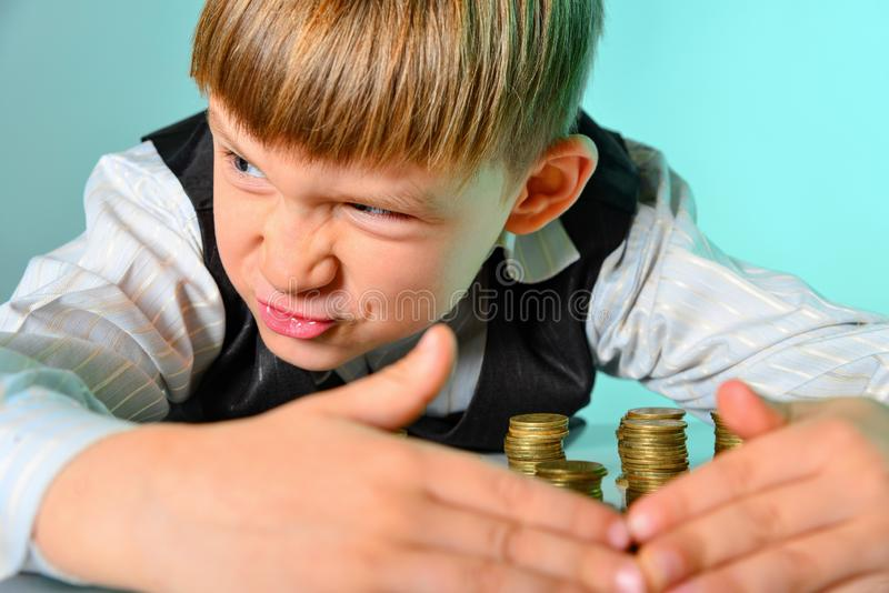 A greedy and greedy rich boy with money looks around, hiding coins from thieves and enemies.  stock images