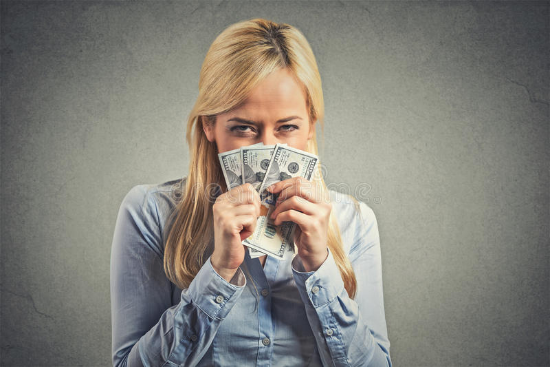 Greedy young woman, holding tight dollar banknotes. Closeup portrait greedy young corporate employee, woman, holding dollar banknotes tight isolated on gray wall stock image