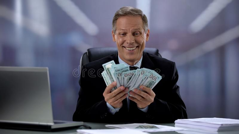 Greedy zakenman met een hoop dollars, blij met gemakkelijk inkomen, hoog salaris stock foto