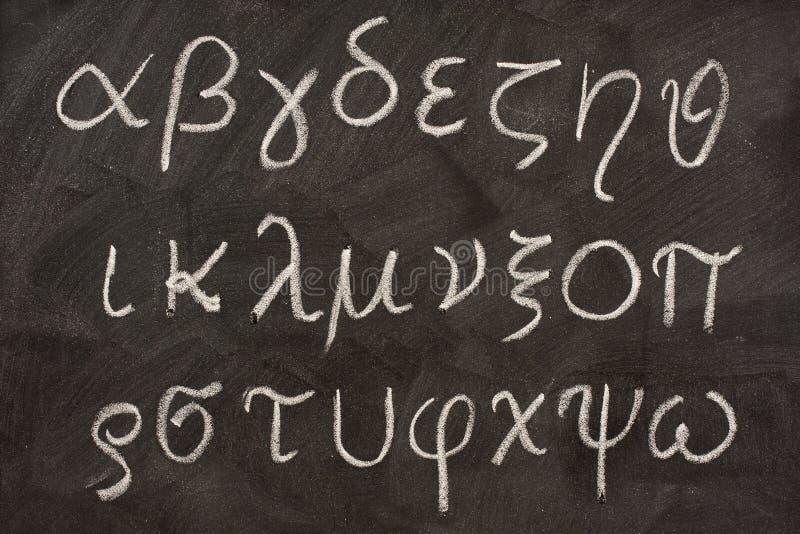 Greek alphabet on blackboard. Twenty four letters of Greek alphabet from alpha to omega (in lower case) handwritten with white chalk on a blackboard stock photography