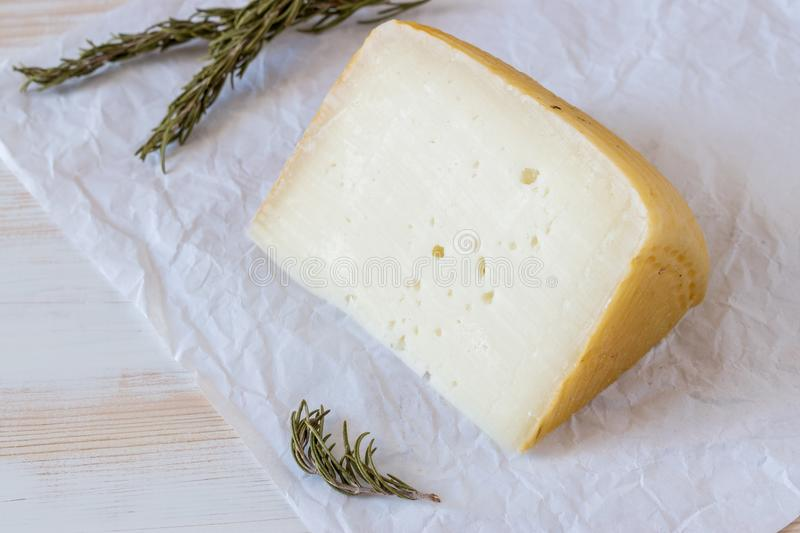 Greek cheese graviera on wooden board with herbs. royalty free stock photos