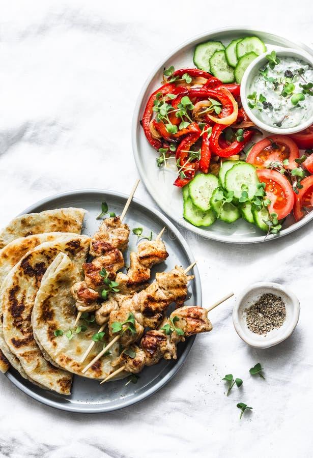Greek chicken skewers, flatbread, tomatoes, cucumber salad, baked sweet pepper, tzatziki yogurt herb sauce on a light background,. Top. Mediterranean style stock image