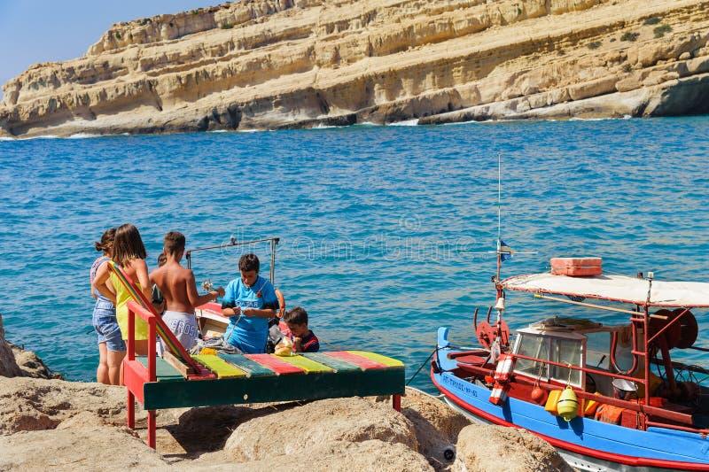 Greek children are catching fish at coast of Matala town on Crete island, Greece. MATALA, GREECE - JUNE 2016: Greek children are catching fish at coast of Matala stock photos