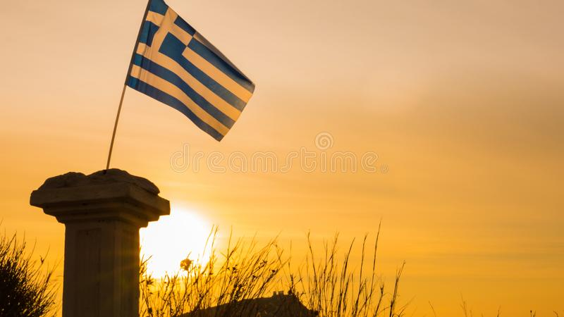 Greek column and flag at sunrise, Cape Sounio. Greece Cape Sounion. Single greek column on sea shore and flag at sunrise, temple of Poseidon in the background stock image