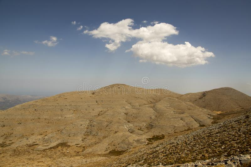 Greek Crete mountain range with highest mountain Ida Psiloritis, very dry hard terrain with sharp rocks and stones, white clouds stock images