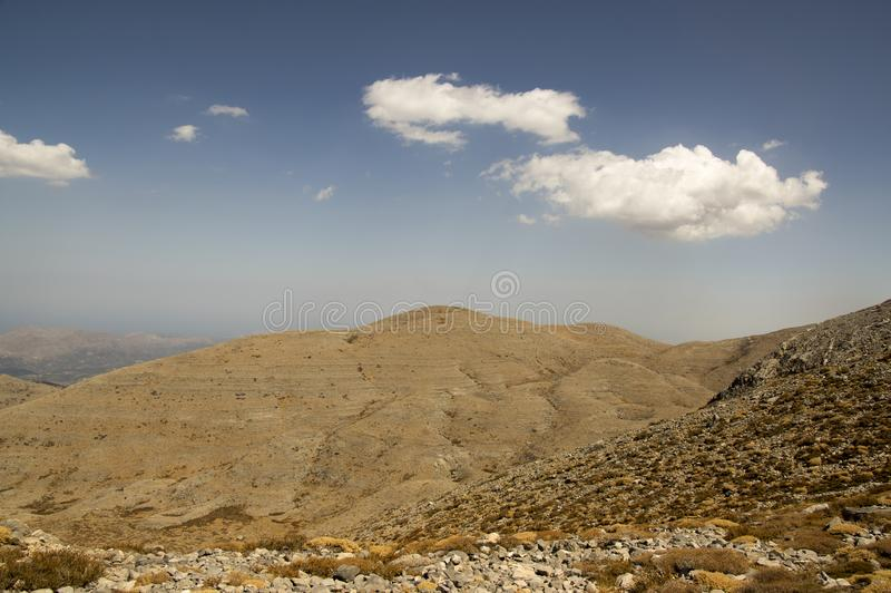 Greek Crete mountain range with highest mountain Ida Psiloritis, very dry hard terrain with sharp rocks and stones, white clouds royalty free stock photography