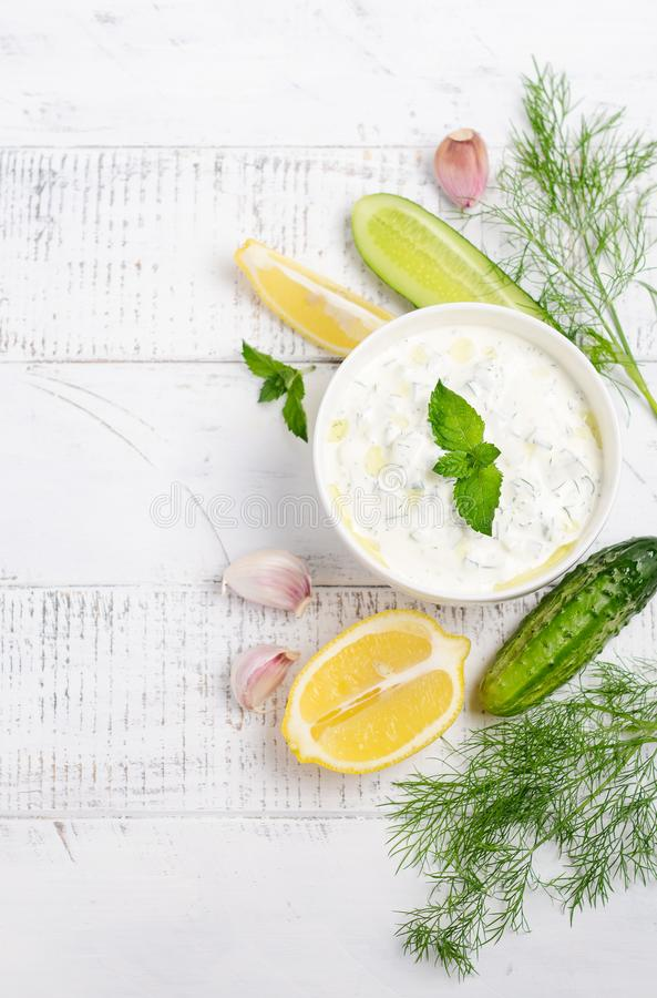 Greek dip sauce or dressing tzatziki and ingredients decorated with olive oil and mint on white wooden table. Top view Flat lay Copy space royalty free stock image