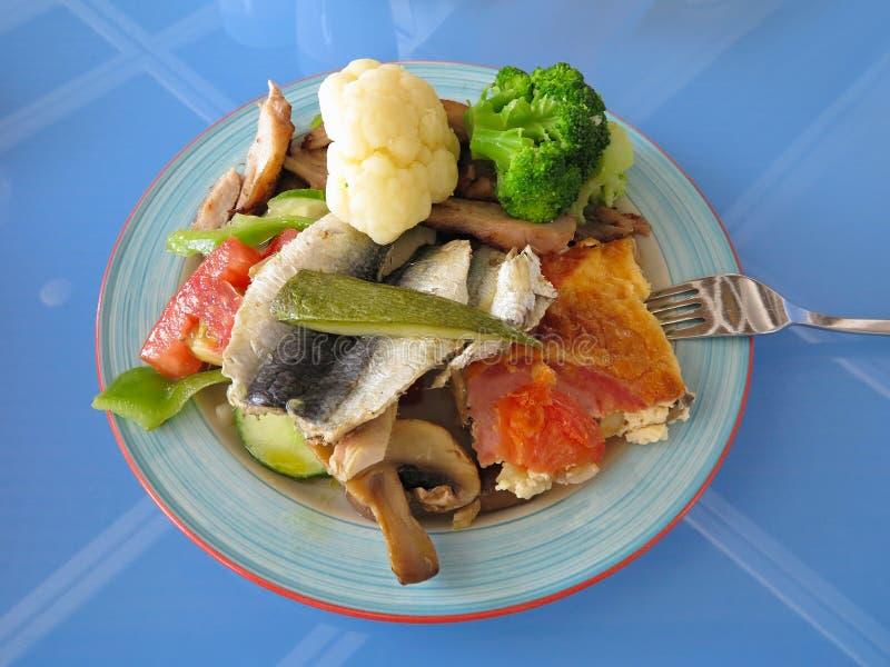 Greek fast food - fish, broccoli, mushrooms on plate royalty free stock photography