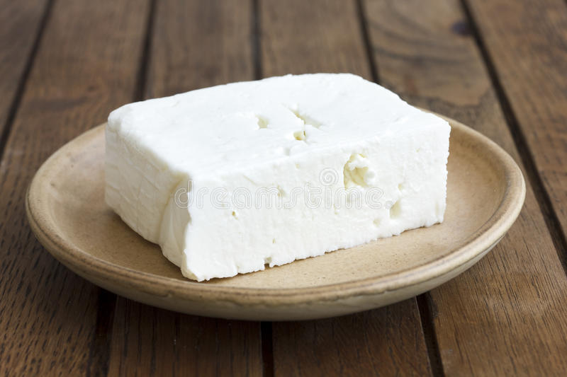 Greek feta cheese block on rustic plate and table. stock images