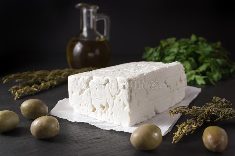 Greek feta cheese on stone board with olives and herbs. stock photos