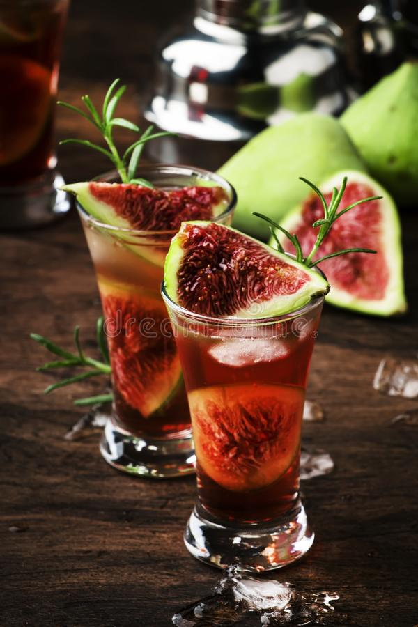 Greek fig tree alcoholic cocktail with cognac, liquor, lime juice, figs and honey, old wooden table, bar tools stock photo