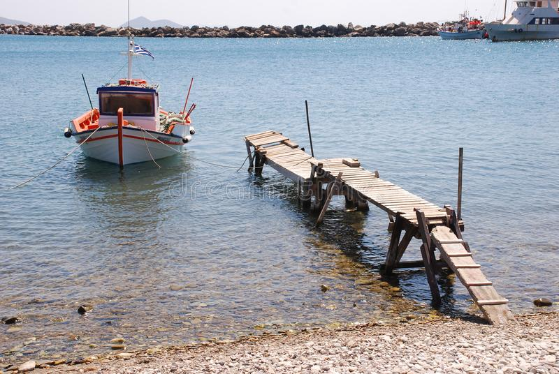 Greek fishing boat moored to a rickety old jetty royalty free stock images