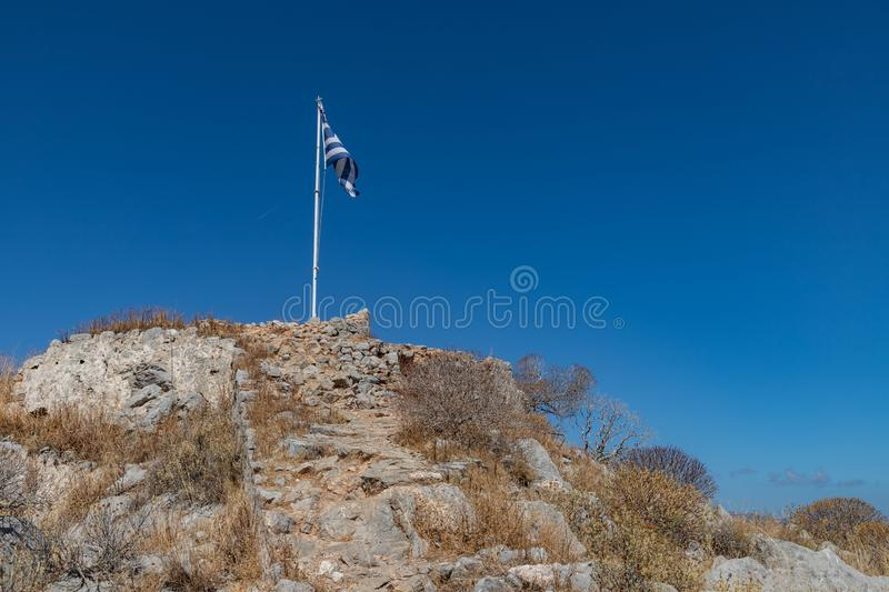 Greek flag and ruins over a mountain in Hydra Island stock photo