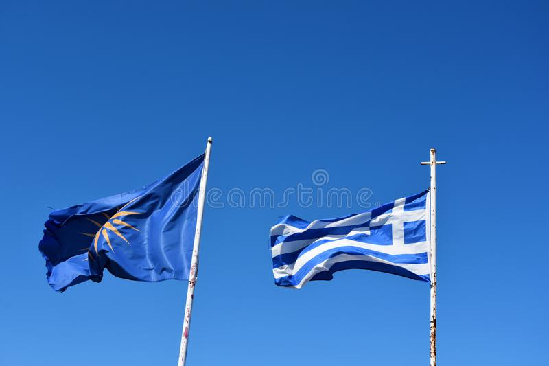 Greek flag and unofficial flag of the Greek region Macedonia. The Vergina Sun on a blue background is commonly used as an unofficial flag of the three royalty free stock photography