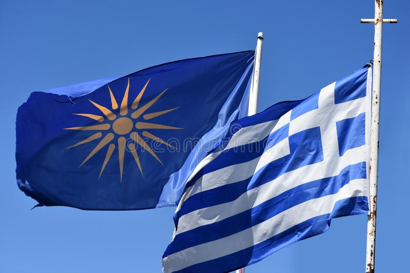 Greek flag and unofficial flag of the Greek region Macedonia. The Vergina Sun on a blue background is commonly used as an unofficial flag of the three royalty free stock image