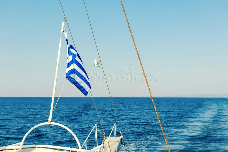 Greek flag waving at the back of a boat. Summer royalty free stock photo