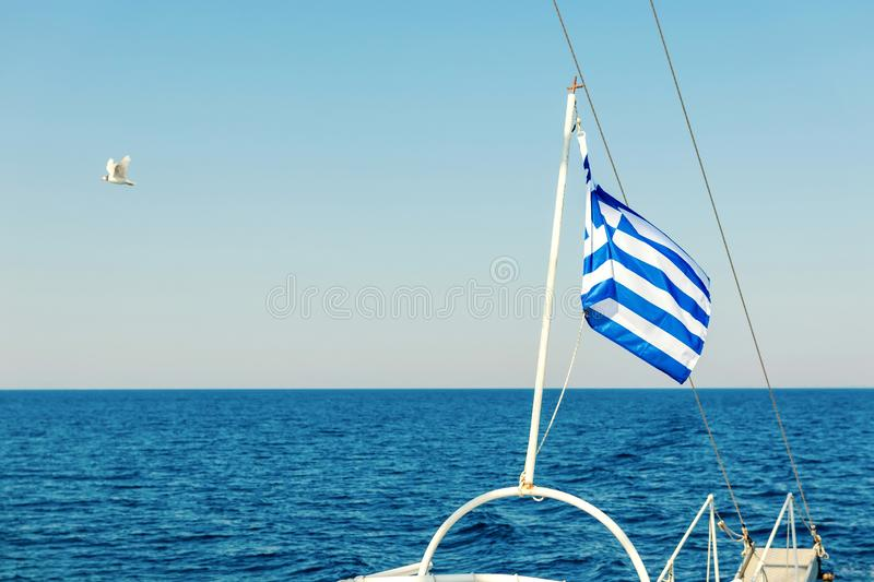 Greek flag waving at the back of a boat. Summer stock images
