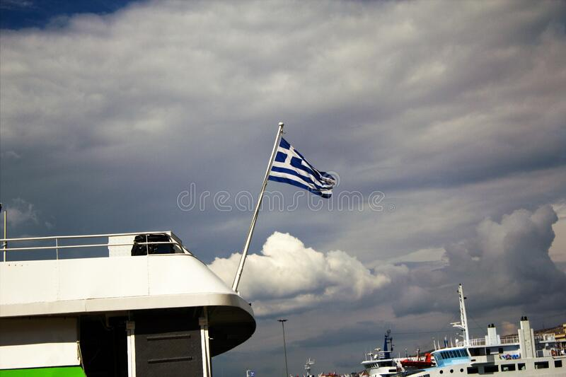 Greek flag waving on a flying cat. At the port of Piraeus in Greece royalty free stock image