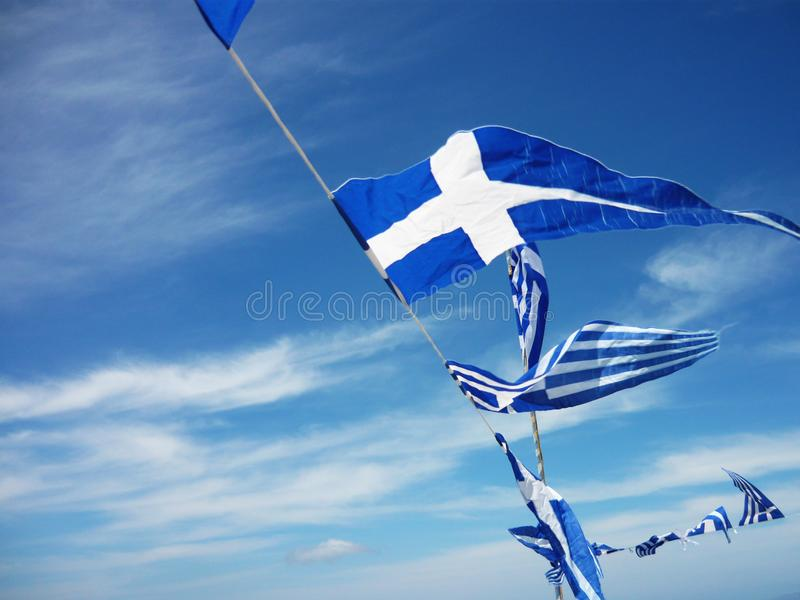 Greek flags flying in the wind. With blue sky and clouds stock image