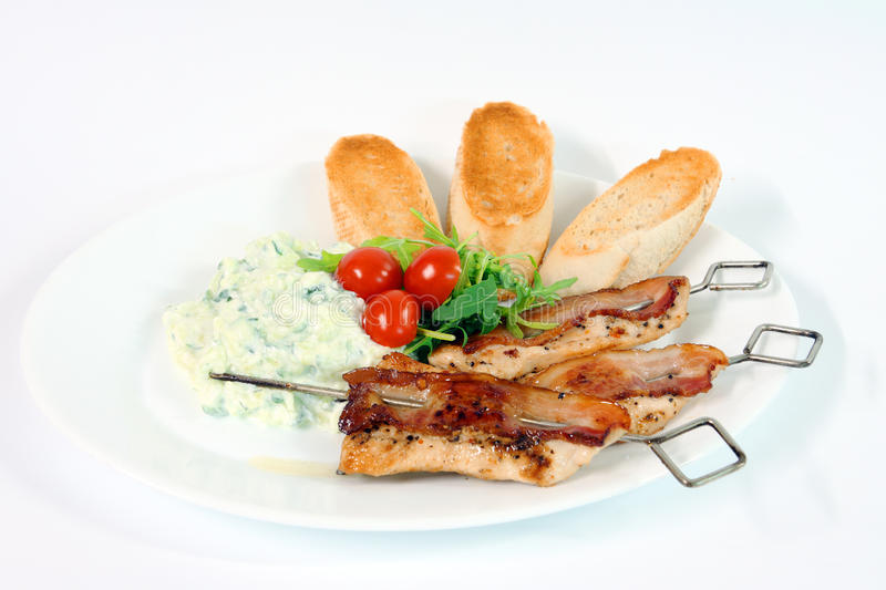 Greek food. Tzatziki, chicken souvlaki with bacon and baguette on white background royalty free stock images