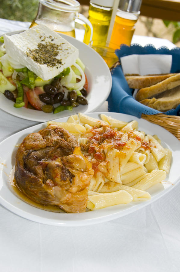 Greek food classic veal stifada with pasta Greek salad crusty br stock photo