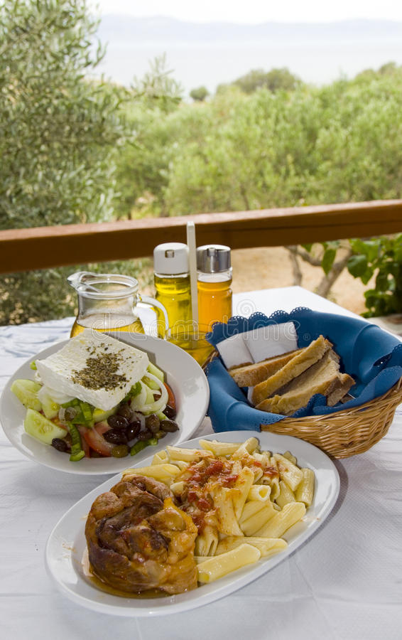 Greek food classic veal stifada with pasta Greek salad crusty br royalty free stock image
