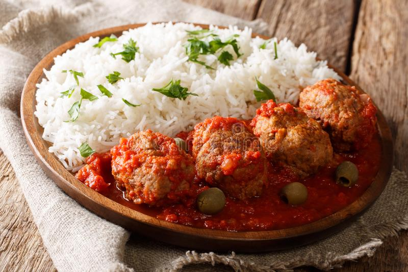 Greek food: Soutzoukakia baked meat balls in spicy tomato sauce. Served with rice close-up on a plate on the table. horizontal stock photo